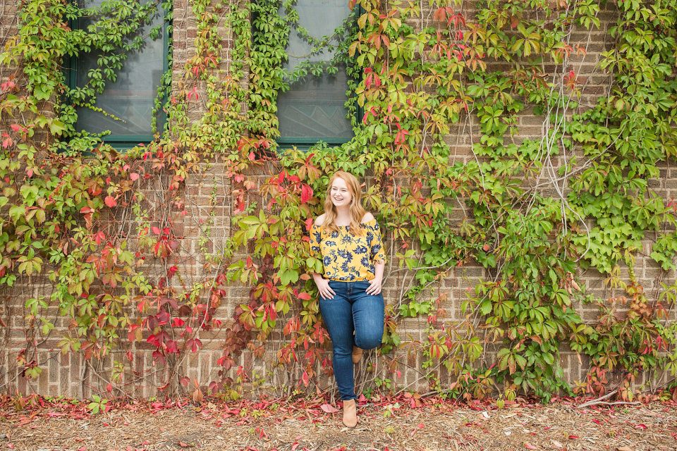 Senior in yellow and blue floral shirt leans against an ivy wall in Downtown Fargo