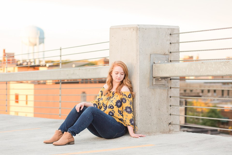 High school senior at the top of a Downtown Fargo parking ramp in blue and yellow floral and jeans