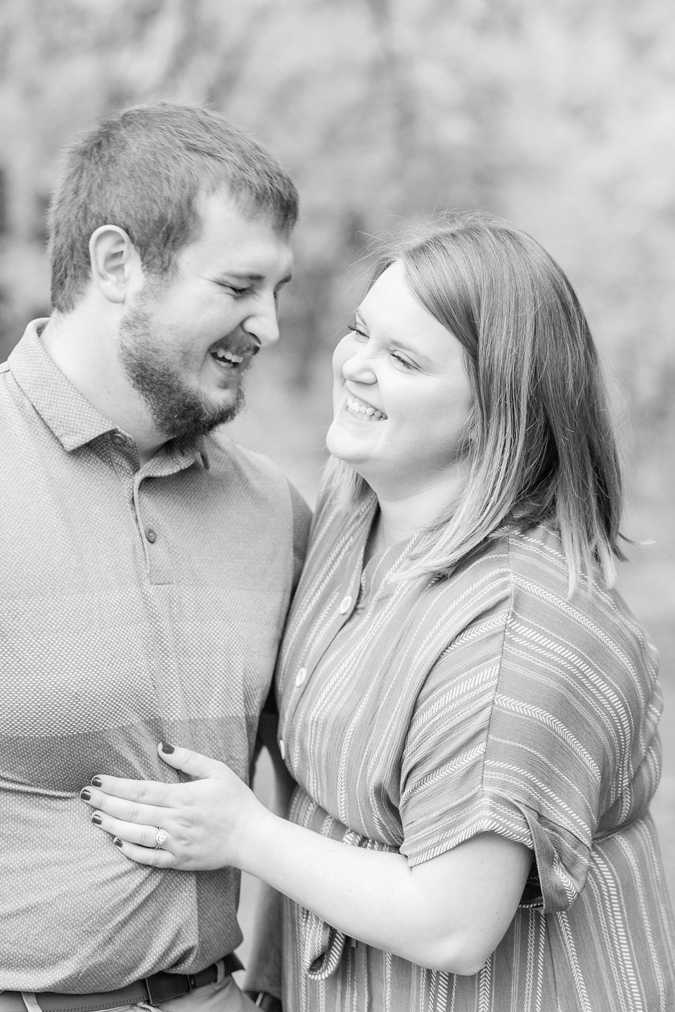An engaged couple laugh at each other during their engagement session