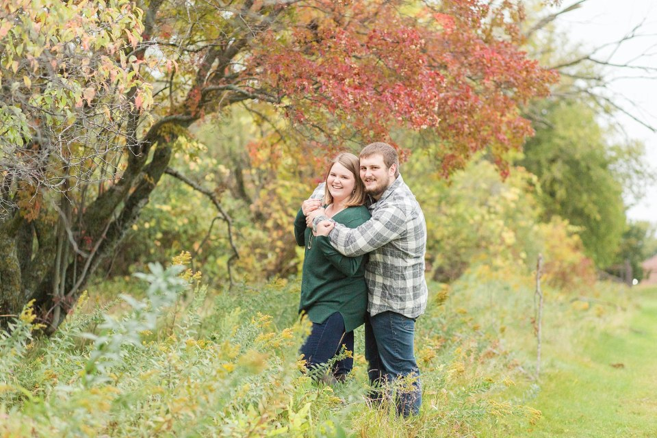 In green and grey plaid, an engaged couple smile in front of a red fall tree