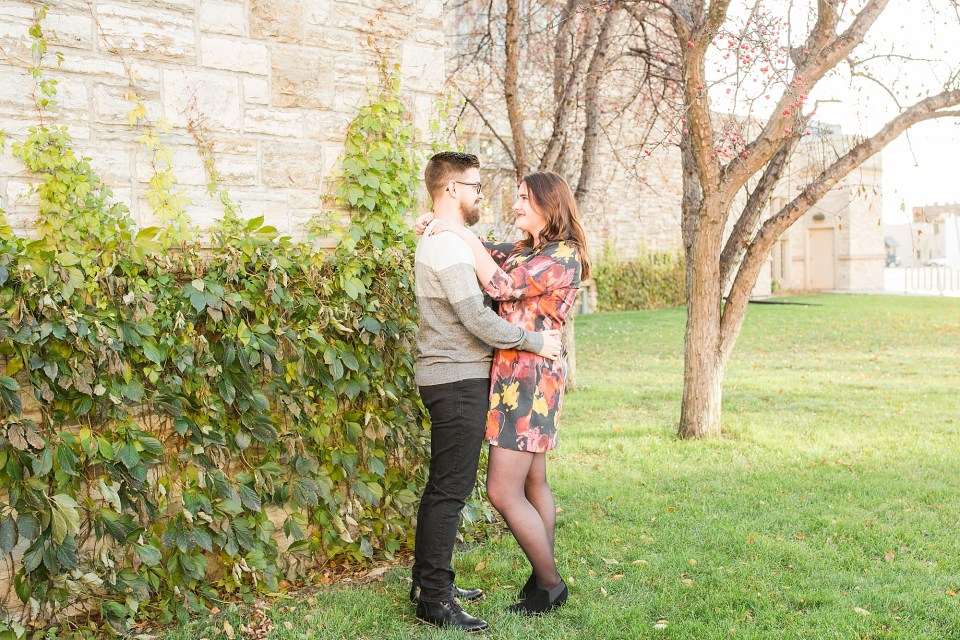 Couple in colorful dress and grey sweater pose for their fall engagement session