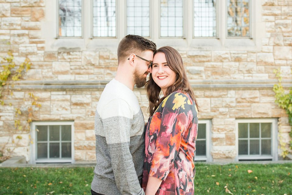 Engaged couple smile in front of a brick church in Downtown Fargo