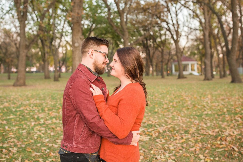 Couple in warm colors go in for a kiss during their colorful fall engagement session