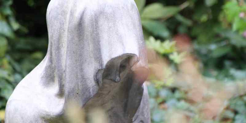 Skulptur auf dem Friedhof Ohlsdorf. Es ist eine Person auf Knien mit Tuch über dem Kopf, bis ins Gesicht gezogen.