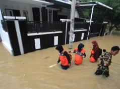 Warga melintasi banjir yang merendam di desa Wanakaya, Kecamatan Gunungjati, Cirebon, Jawa Barat, Sabtu (8/2/2020).