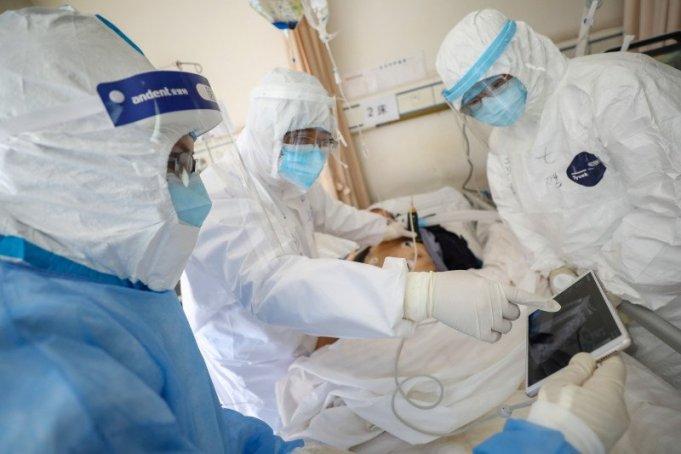 Para pekerja medis dengan mengenakan pakaian pelindung memeriksa seorang pasien di dalam bangsal terisolasi Rumah Sakit Palang Merah Wuhan di Wuhan, pusat penyebaran wabah virus corona baru, di Provinsi Hubei, China, 16/2/2020. ANTARA/China Daily/ via REUTERS/tm
