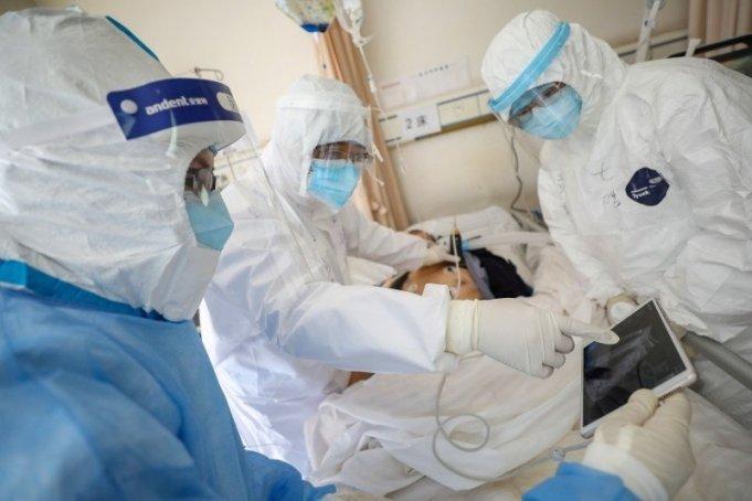 Para pekerja medis dengan mengenakan pakaian pelindung memeriksa seorang pasien di dalam bangsal terisolasi Rumah Sakit Palang Merah Wuhan di Wuhan, pusat penyebaran wabah virus corona baru, di Provinsi Hubei, China, 16/2/2020. (ANTARA/China Daily/ via REUTERS/tm)