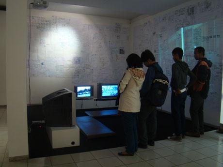 Beberapa pengunjung pameran sedang melihat karya video Forum Lenteng