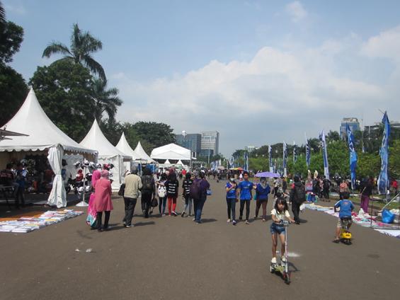 Suasana siang hari di Monas, para pengunjung berjalan-jalan di sekitar tenda-tenda pameran/jualan.