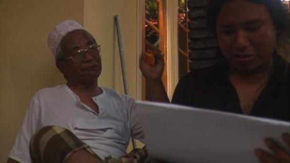 Salah satu adegan dalam Filem Elesan Deq a Tutuq: Tuan Guru (kiri) dan si seniman muda.