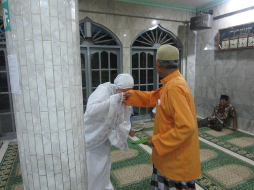 Pak Edy (baju oranye), salah seorang panitia zakat, sedang memberikan santunan anak yatim dari hamba Allah.