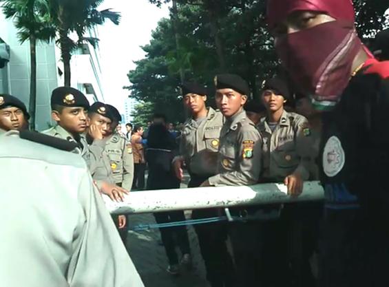 Si Jurnalis Kompas TV masuk kembali ke halaman gedung KPK, melewati gerbang yang dijaga petugas polisi.
