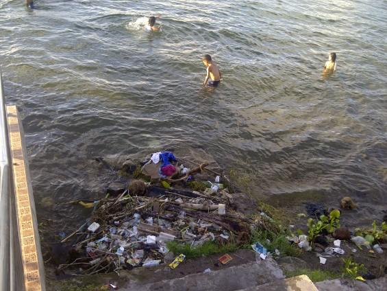 Unggukan sampah yang tak jauh dari Wisatawan yang sedang mandi di dermaga apung Danau Singkarak (tahun 2013).