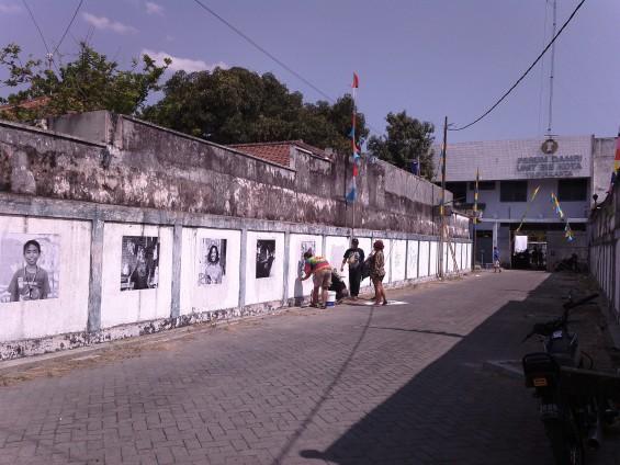 Seniman-seniman KALEIDOSKOP menempel poster di dinding di area jalan masuk ke gedung DAMRI.