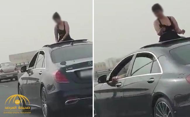 شاهد .. فتاة تتمايل وهي تطل من فتحة سيارة برفقة شاب على جسر ستره بالبحرين