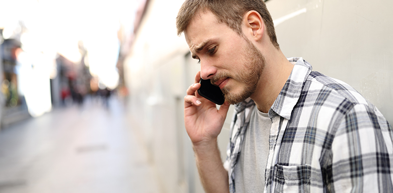 Upset man calling for help with cell phone