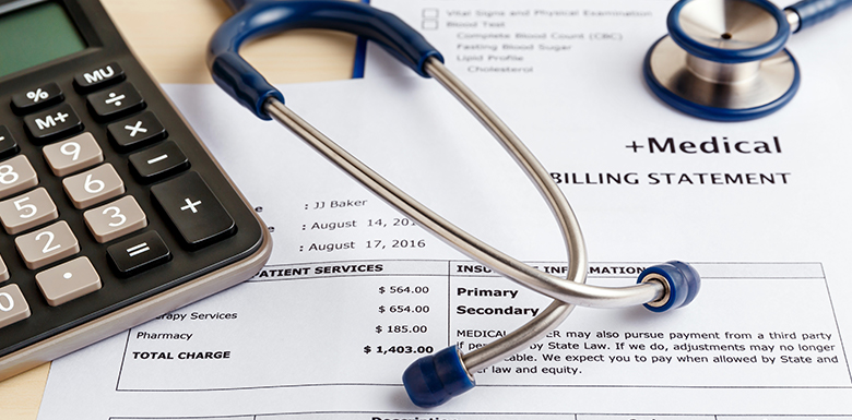 Stethoscope on top of medical bill papers with calculator