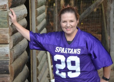 Jami Davis, Mandy's mother, leans on a chicken coop at the family's hatchery. (Solomon Crenshaw Jr./Alabama NewsCenter)