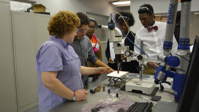 Huffman and Vestavia Hills high school students use microscopy to inspect various objects with Kelly Davis, advanced engineering technician.