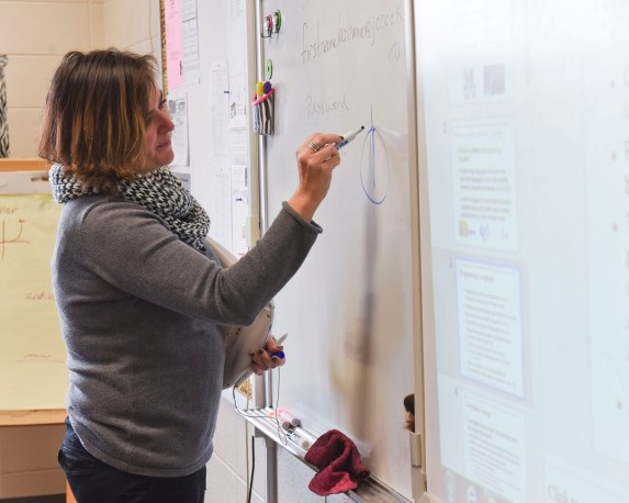 Nidia Fernandez-Lee draws a symbol on a whiteboard while describing coding. (Frank Couch / Alabama NewsCenter)