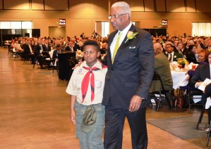 "A Boy Scout leads Birmingham Mayor William Bell to the state to receive his ""Heart of the Eagle"" award. (Michael Tomberlin/Alabama NewsCenter)"