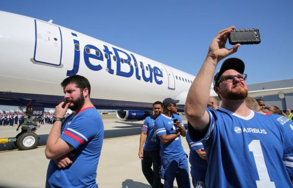 Employee Kevin Powell, right, records the delivery ceremony Monday, April 25, 2016, for JetBlue A321 Ð the first Airbus aircraft produced at Airbus U.S. Manufacturing Facility in Mobile, Ala. (Mike Kittrell/Alabama NewsCenter)