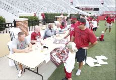 Players and coaches sign autographs during Fan Day at the University of Alabama football practice. (Amelia B. Barton / Alabama NewsCenter)