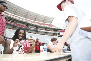 Outside linebacker Tim Williams signs autographs for fans. (Amelia B. Barton / UA Athletics)