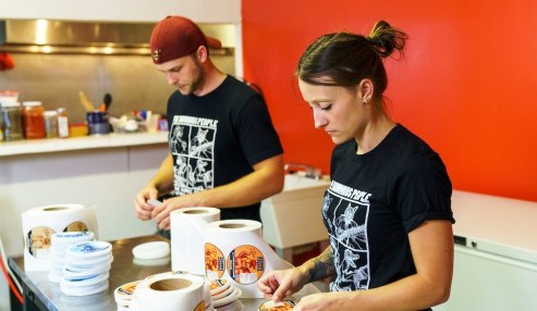 Colin Woltmann and Allie Clark paste labels in their company's Athens headquarters. Each flavor comes with a recommendation for appropriate beer and music to accompany it. (Mark Sandlin/Alabama NewsCenter)