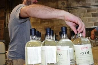 Redmont Distilling co-founder Jake Hendon puts labels on bottles of Alabama Cotton Gin. (Michael Tomberlin / Alabama NewsCenter)