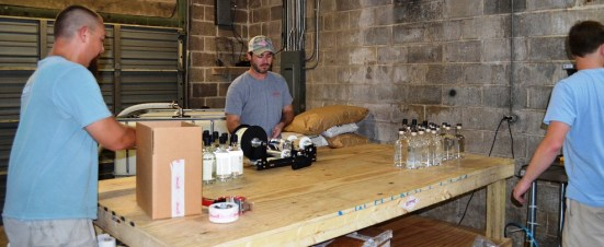 Jonathan Guidry, left, packages while Jake Hendon, center, labels and Stephen Watts, right, bottles Alabama Cotton Gin. The three partners founded Redmont Distilling and handle all of the work producing spirits. (Michael Tomberlin / Alabama NewsCenter)