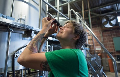Brewer Jessica Moses checks sugar levels on beer brewing at the Back Forty Beer Co. in Gadsden. (Bernard Troncale / Alabama NewsCenter)