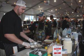 Flora-Bama team members Jared Gibbs-and Haikel Harns prepare dish in seafood competition. (Robert DeWitt/Alabama NewsCenter)