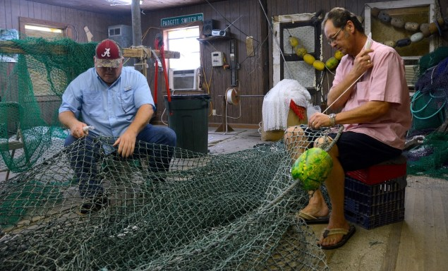 Steve Sprinkle and Henry Barnes work on a net in Sprinkle's Bayou La Batre shop. Sprinkle's nets are handmade for top performance, he says. (Karim Shamsi-Basha/Alabama NewsCenter)