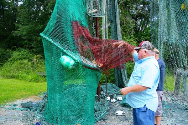Steve Sprinkle displays one of the handmade shrimp nets hanging outside his shop. (Karim Shamsi-Basha/Alabama NewsCenter)