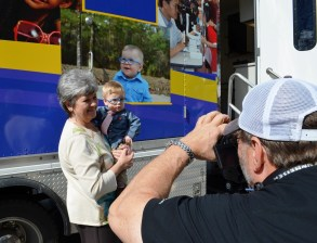 Gunner Hewitt gets his picture made in front of the Alabama Lions' Mobile Eye and Vision Clinic, which sports an image of Gunner on its side. (Michael Tomberlin/Alabama NewsCenter)