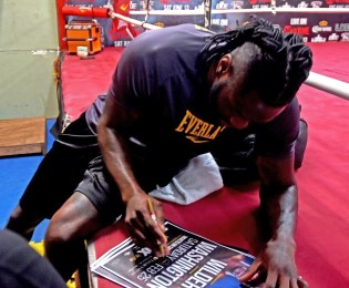 Deontay Wilder signs a fight poster for a fan at Skyy Gym. (Solomon Crenshaw Jr./Alabama NewsCenter)