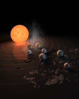 This artist's concept appeared on the February 23rd, 2017 cover of the journal Nature announcing that the TRAPPIST-1 star, an ultra-cool dwarf, has seven Earth-size planets orbiting it. Any of these planets could have liquid water on them. Planets that are farther from the star are more likely to have significant amounts of ice, especially on the side that faces away from the star. (NASA/JPL-Caltech)