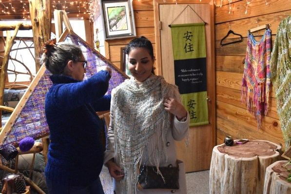 Silvia Costantino adjusts a shawl at her Mentone shop, Hummingbird at Loom. (Karim Shamsi-Basha/Alabama NewsCenter)