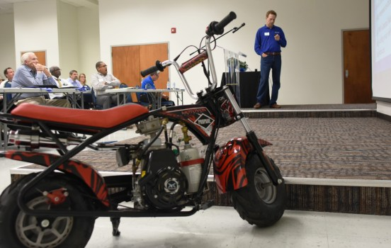 Buddy Gamel with Precision Sales & Service touts the advantages of propane during Odyssey Day at Lawson State Community College. In the foreground is a propane-powered scooter that Gamel rode into the lecture hall. (Solomon Crenshaw Jr./Alabama NewsCenter)