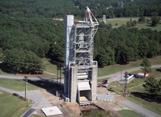 Marshall Space Flight Center's F-1 Engine Test Stand is shown in this picture. Constructed in 1963, the test stand is a vertical engine firing test stand, 239 feet in elevation and 4,600 square feet in area at the base, and was designed to assist in the development of the F-1 Engine. Capability is provided for static firing of 1.5 million pounds of thrust using liquid oxygen and kerosene. The foundation of the stand is keyed into the bedrock approximately 40 feet below grade. (Photo Credit: NASA)