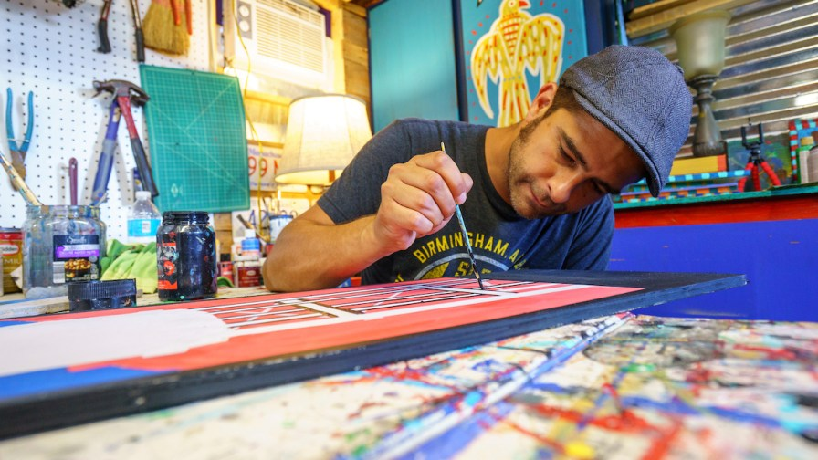 Anthony Tavis works on a painting of the Sloss water tower in his Helena studio. (Mark Sandlin/Alabama NewsCenter)