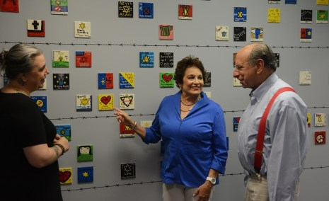 Cathy Friedman talks with Rebecca Dobrinski and Joel Rotenstreich at a wall of memorial tiles at the Birmingham Holocaust Education Center. (Karim Shamsi-Basha/Alabama NewsCenter)