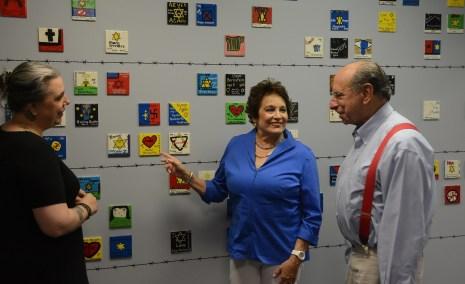 Cathy Friedman talks with Rebecca Dobrinski and Joel Rotenstreich at a wall of memorial tiles at the Birmingham Holocaust Education Center. (Karim Shamsi-Basha/Alabama NewsCenter)
