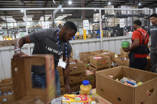 SEC athletes work to pack 3,500 meals that will feed hungry people through the Community Food Bank of Central Alabama. (Karim Shamsi-Basha/Alabama NewsCenter)