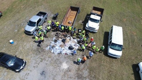 A work crew surrounds a mound of trash and debris pulled from Valley Creek in Midfield. (Freshwater Land Trust)