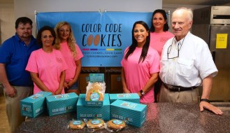 The Color Code Cookies artisans, flanked by chef JK Turnipseed, left, and president Jim Turnipseed, right. (Karim Shamsi-Basha/Alabama NewsCenter)