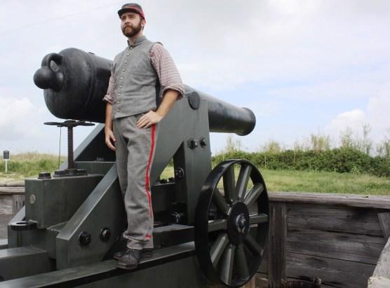 Dylan Tucker stands with the Fort Morgan's restored 32-pounder artillery piece. (Robert DeWitt / Alabama NewsCenter)