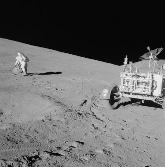 "(31 July 1971) – Astronaut Dave Scott, commander, with tongs and gnomon in hand, studies a boulder on the slope of Hadley Delta during the Apollo 15 lunar landing mission's first extravehicular activity (EVA). The Lunar Roving Vehicle (LRV), ""Rover,"" is in the right foreground. (Photograph by astronaut James B. Irwin, lunar module pilot, NASA)"