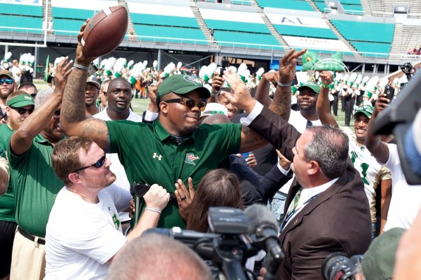 Timothy Alexander walks with assistance to deliver the game ball for UAB football's return at Legion Field. (Aaron Grayson / Alabama NewsCenter)